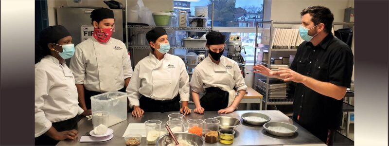 St. Louis culinary students working with chef teacher on a recipe